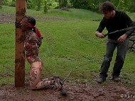 Crazy villager tied up brunette girl to a pole, pelted her with mud, and spanked small buttocks