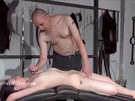 Парень наказывает молодую брюнетку ударами плётки и втыканием игл в спину