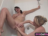 Cheerful girlfriends gently massage with fingers each other's cunny in the shower