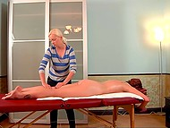 Red-haired colleen relaxes and takes pleasure from gentle movements of masseuse's hands