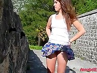 Ветер развевает короткую юбочку молодой извращенки, не надевшей трусиков перед этой прогулкой