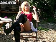 Блондинка в высоких сапогах закурила сигарету и как бы невзначай засветила киску без трусиков