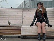 Russian model in short skirt without panties sits on bench in park and speaks with dove