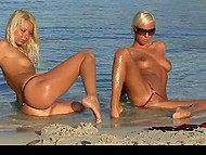 Blonde girls with sexy tanned bodies don't mind posing to photographer on the beach