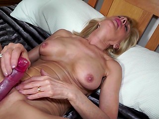 Amateur mature in sexy lingerie pleases herself by shoving red vibrator into her snatch