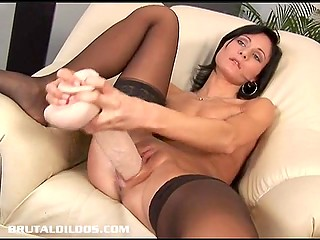 Wide vagina of black-haired masturbatrix stretches to limit under huge dildo pressure