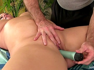 Gray-haired masseur relaxes chubby brunette client using skillful hands and his favorite vibrator