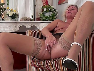 Slim blonde mature Ellen B undresses to finger and touch her unshaved vagina alone in living room