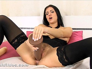 Relaxed brunette in black stockings thrusts impressive dildo straight into her unshaved vagina