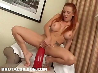 Red-haired cougar with round tits not shy to thrust some giant dildos into her trimmed snatch and ass