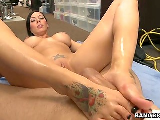 Long-legged brunette with round melons strokes partner's phallus using only her oiled up feet