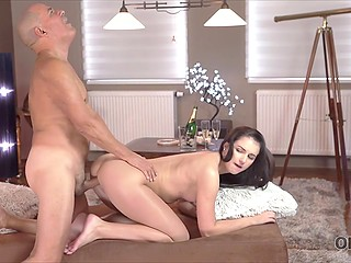 Old benefactor gives brunette girl champagne with refined taste and they have sex on the couch