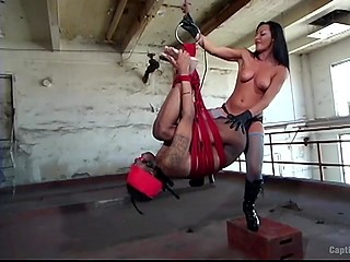 Raven-haired mistress satisfies sexual needs and treats ass of black slave with strapon