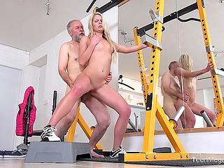 Хитрый старик помогает юной блондинке с растяжкой и за это награждается сексом в пустом зале