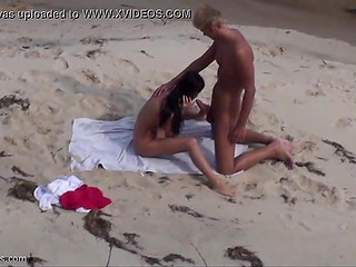 Babe feels so good that doesn't pay attention to voyeur who films sex on the beach